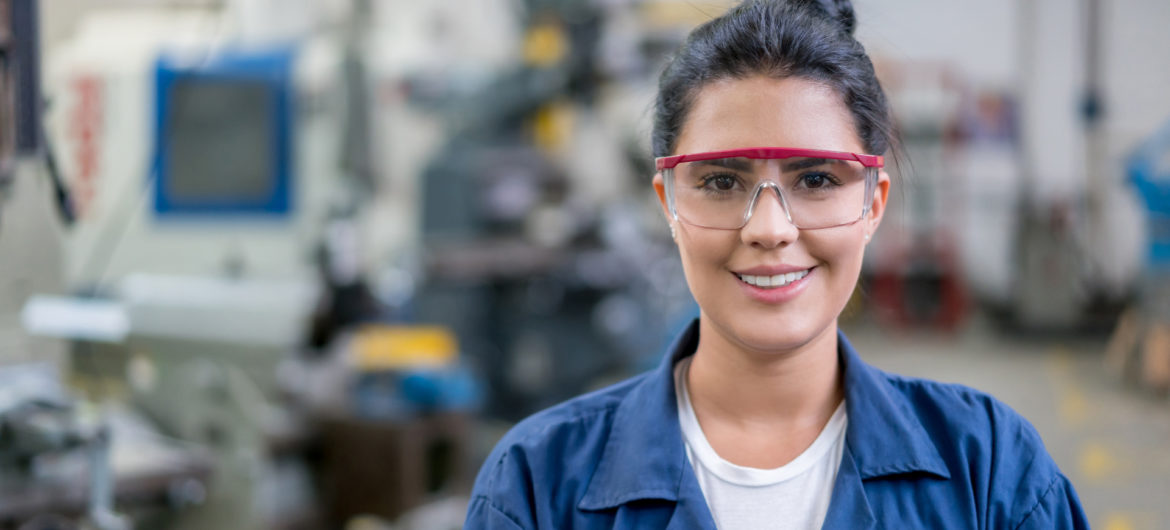 Portrait of a female engineering student in a workshop looking at the camera smiling - education concepts